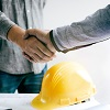 Image of two men shaking hands above a hard hat