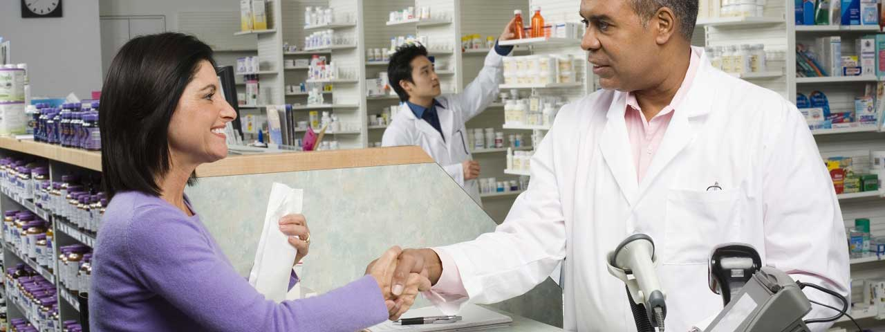 Pharmacist shaking hands with customer
