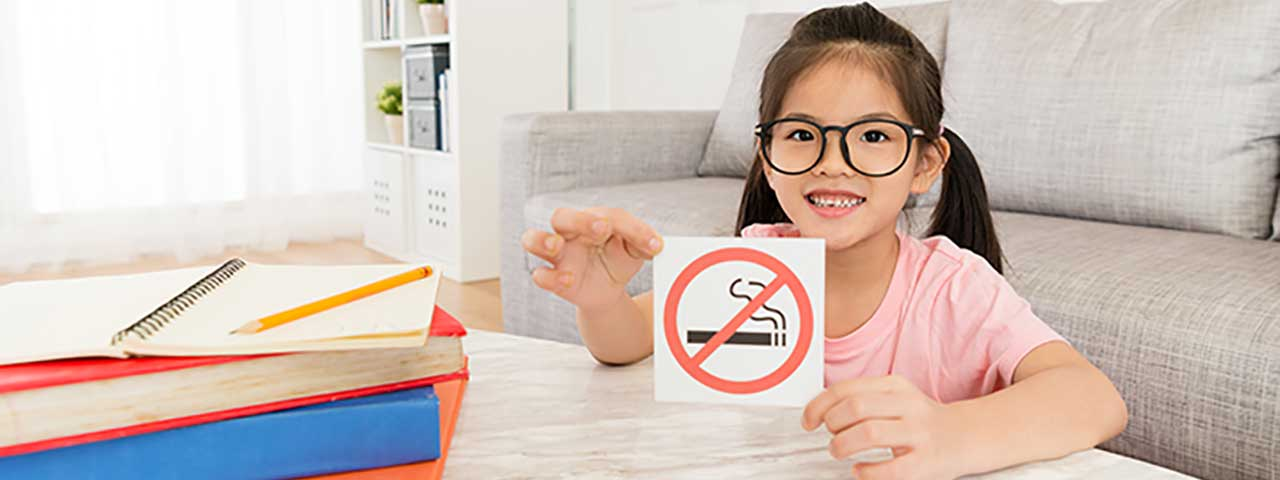 Girl holding no smoking sign