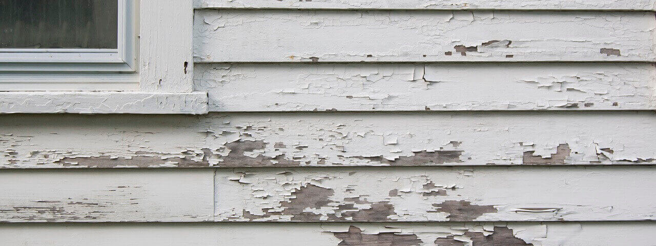 Image of the exterior of a house, which shows cracked and peeling paint.