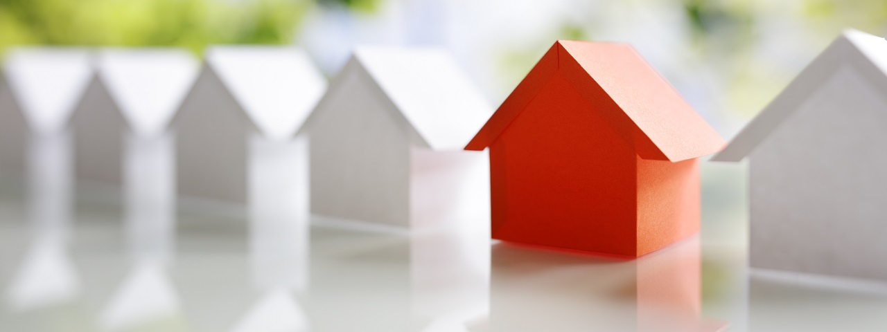 Conceptual image of a row of houses, one of which is red