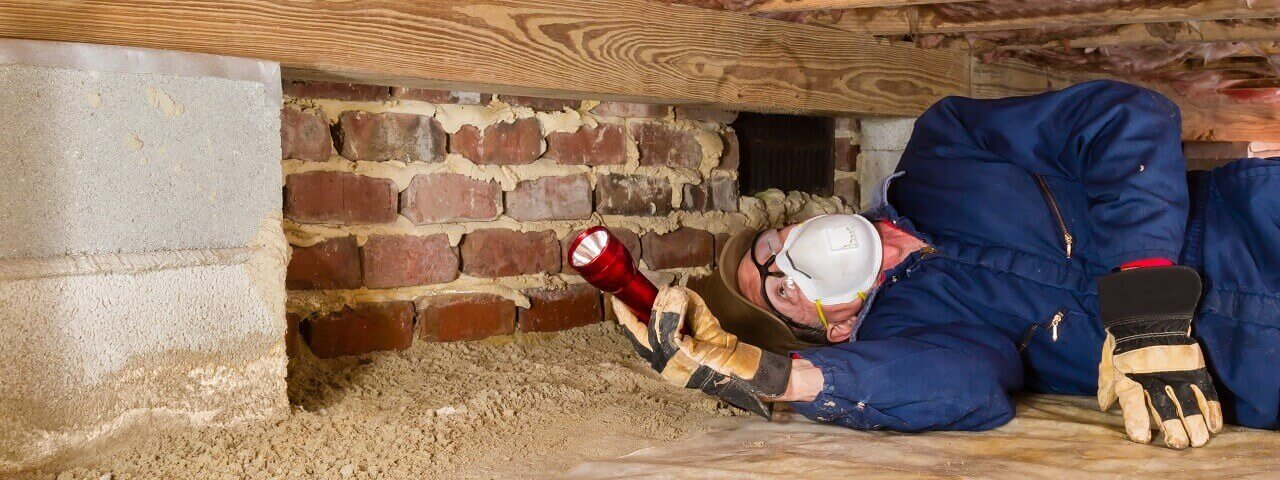 Worker in a mask searches a crawl space