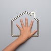 Conceptual image of a child's hand on the outline of a house