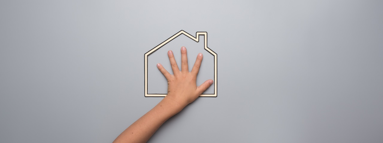 Conceptual image of a child's hand resting on the outline of a house