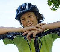 Child on bicycle with helmet on.