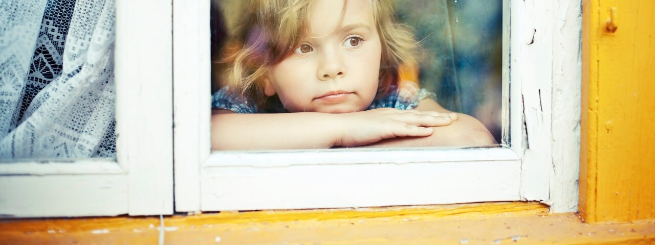 Image of a young girl staring out a window that has cracking paint on the outside